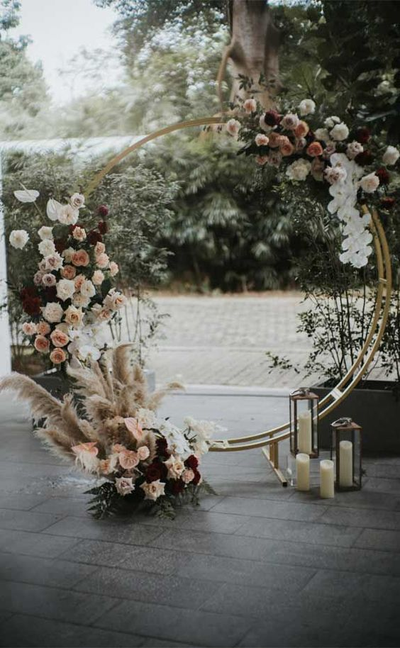 a modern refined round wedding arch with pampas grass, blush, white and burgundy blooms and some foliage plus candles