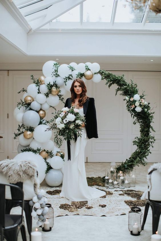 a modern round wedding arch done with greenery and white blooms plus white and gold balloons for a modern wedding