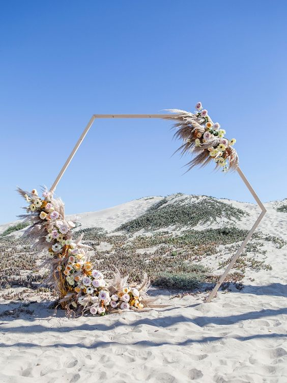a pastel hexagon wedding arch decorated with pampas grass, light pink, white and yellow flowers is amazing