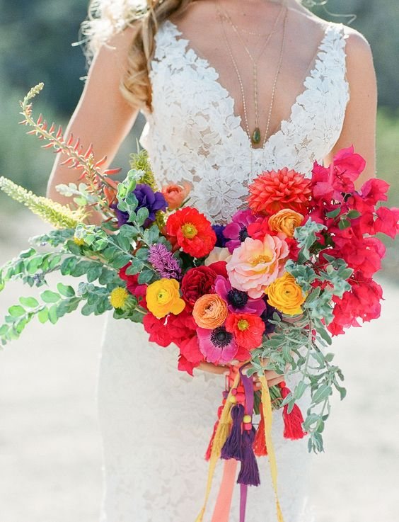 a pretty and bright wedding bouquet with red, blush, yellow and orange blooms, greenery and fillers that add dimension