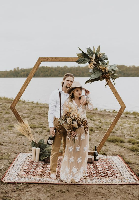 a pretty boho wedding arch decorated with neutral blooms, oversized leaves, wheat and candles for a boho couple