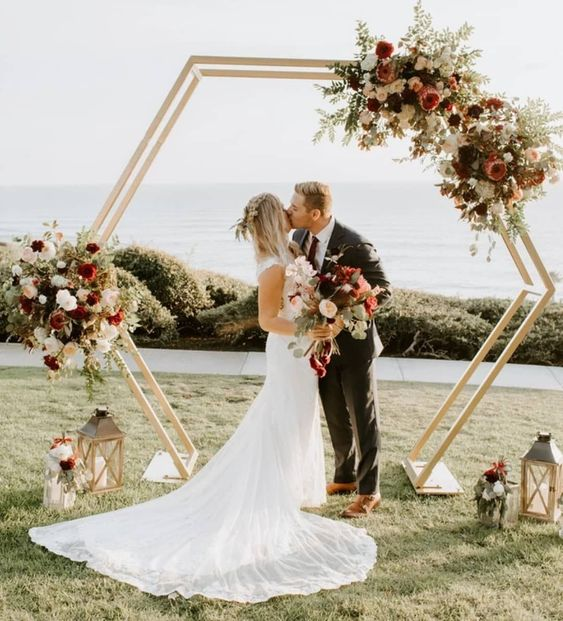 a pretty hexagon boho wedding arch with greenery, white, peachy and burgundy blooms and candle lanterns for a fall wedding