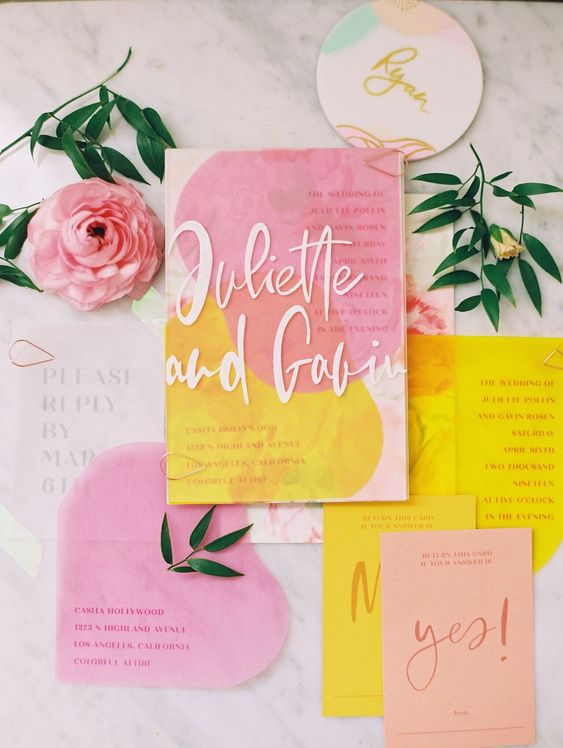 a pretty tropical wedding invitation suite with pink and yellow items and watercolors, with cool lettering