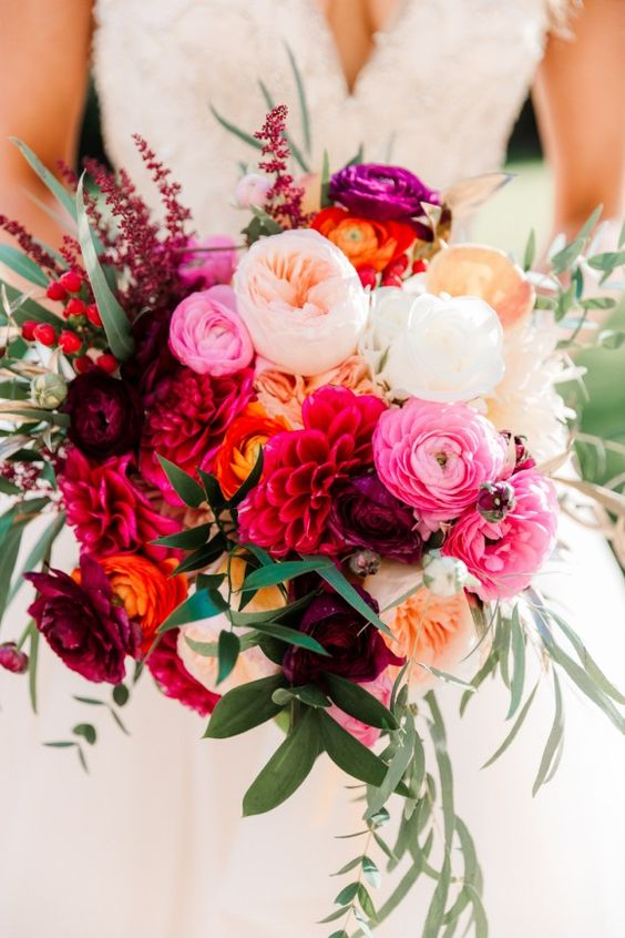 a refined and bold wedding bouquet with red, purple, pink, blush and yellow blooms and some greenery and berries