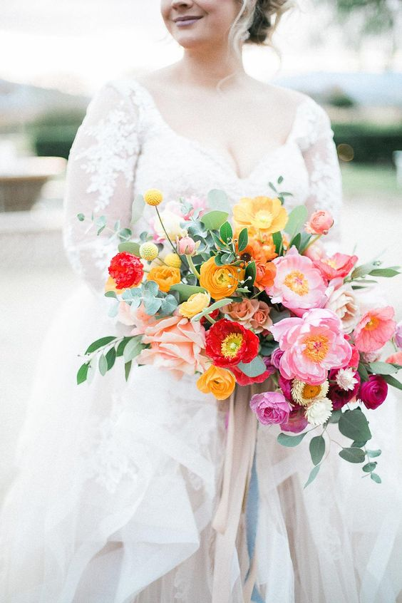 a refined and chic colorful wedding bouquet with yellow, red, pink and hot pink blooms, greenery and long neutral ribbons