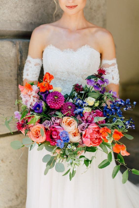 a refined wedding bouquet with pink, red, fuchsia, purple and blue blooms and foliage is a lovely idea for a colorful wedding
