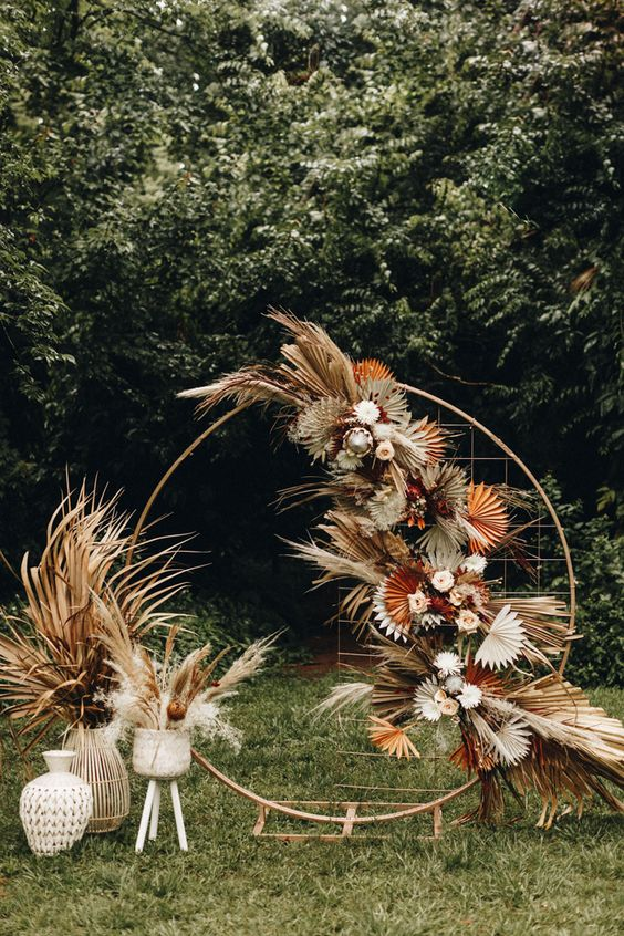a round wedding arch with gold mesh, gilded fronds and grasses, blush and white blooms