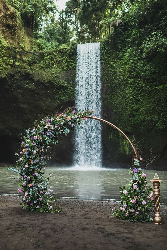 a round wedding arch covered with greenery, blush, lilac and pink blooms and with a waterfall backdrop