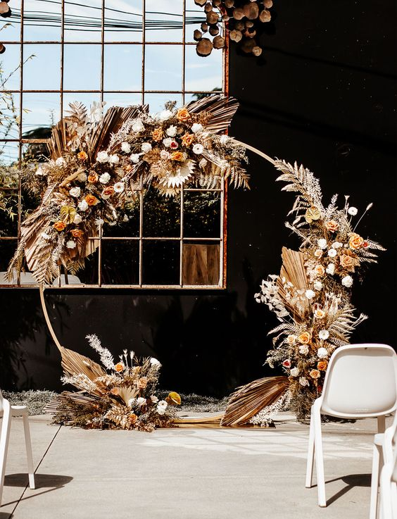 a round wedding arch with white and rust blooms, gilded foliage and fronds is a very refined idea for a boho wedding