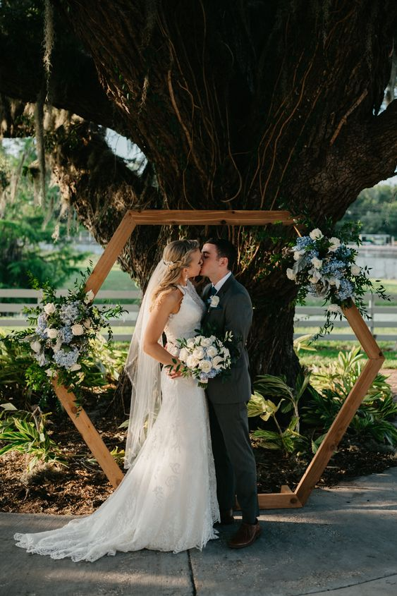 a spring hexagon wedding arch with greenery, white and blue flowers is a lovely idea for a spring wedding
