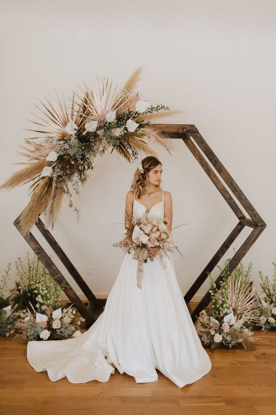 a stained hexagon wedding arch decorated with pampas grass, greenery, white blooms and fronds for a boho wedding