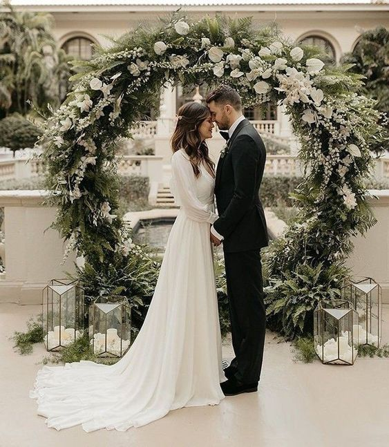 a stunning round wedding arch covered with greenery and white blooms all over, candle lanterns on the floor