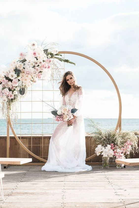 a stylish modern glam wedding arch with mesh, white and light pink blooms and greenery is gorgeous