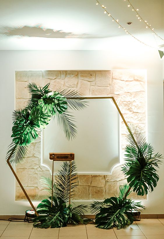 a tropical hexagon wedding arch decorated with large fronds is a pretty idea for a modern tropical wedding