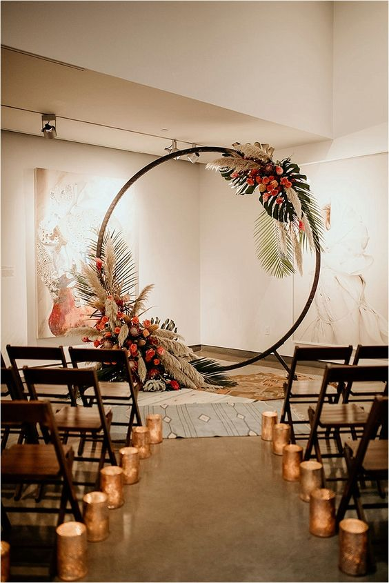 a tropical round wedding arch with fronds, leaves, pampas grass, pink and blush blooms is a lovely boho idea