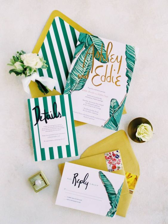 a vibrant tropical wedding invitation suite in emerald and mustard, with amazing tropical and stripe prints