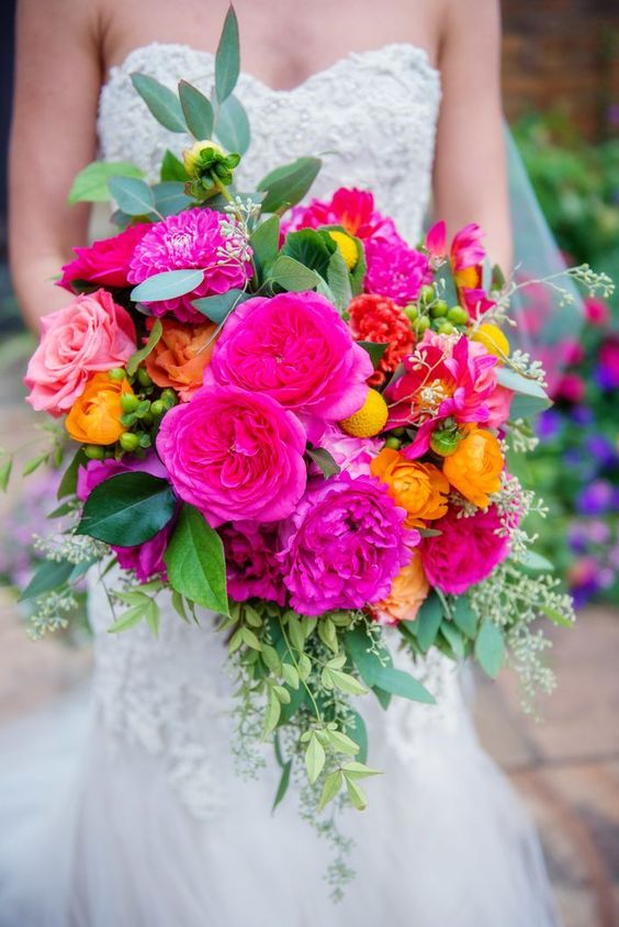 a vibrant wedding bouquet with hot pink, light pink, honey yellow, billy balls, greenery is a cool and bold idea