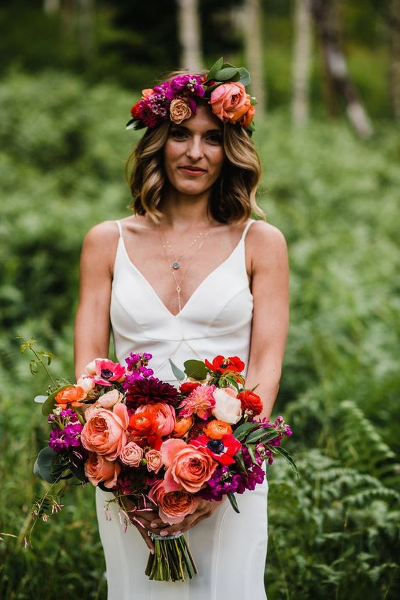 a vibrant wedding bouquet with pink, red, orange, burgundy and purple blooms and greenery