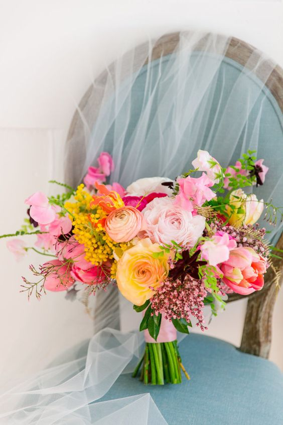 a vibrant wedding bouquet with pink, yellow, blush blooms, deep purple ones and yellow ones plus some greenery