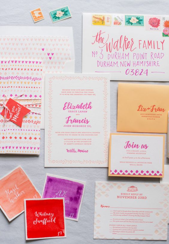 a vibrant wedding invitation suite in hot pink, red, orange and yellow with colorful patterns is fun