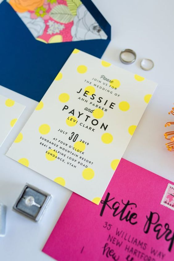 a vibrant wedding invitation suite with a navy and hot pink envelope, a polka dot invite and floral lining