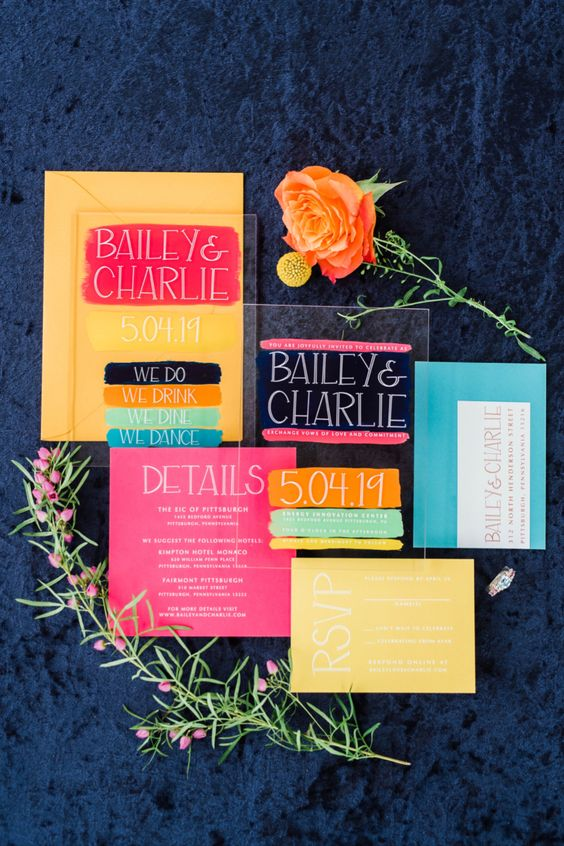 a whimsy and colorful wedding invitation suite done in yellow, blue, hot pink and orange plus an acrylic invitation is fun