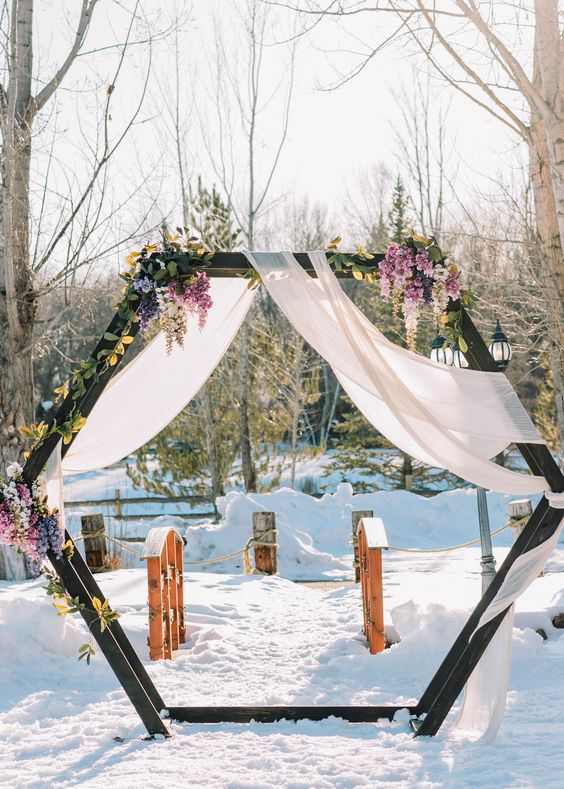 a winter hex wedding arch with blush fabric, pink, purple and yellow blooms and greenery is an amazing idea
