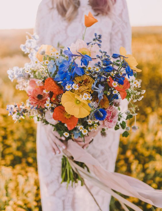 an amazing bold wedding bouquet with blue, red, yellow and white flowers and long pastel ribbons for a wildflower wedidng