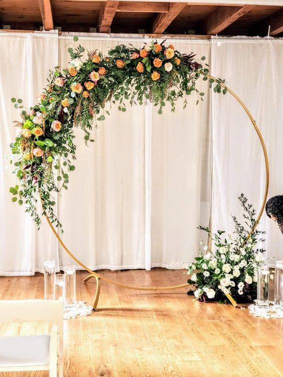an elegant round wedding arch with greenery, orange, peachy and white blooms and floating candles