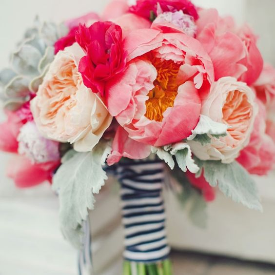 a bold peachy peony roses and pink peony wedding bouquet with pale foliage for a nautical wedding