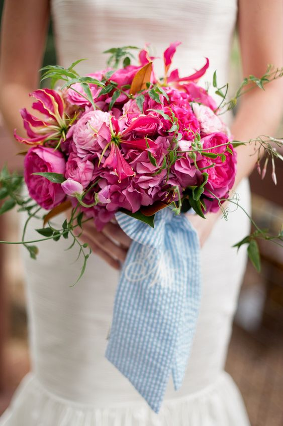 a super bold hot pink wedding bouquet of peonies and ranunculus, some greenery and wide blue striped ribbons