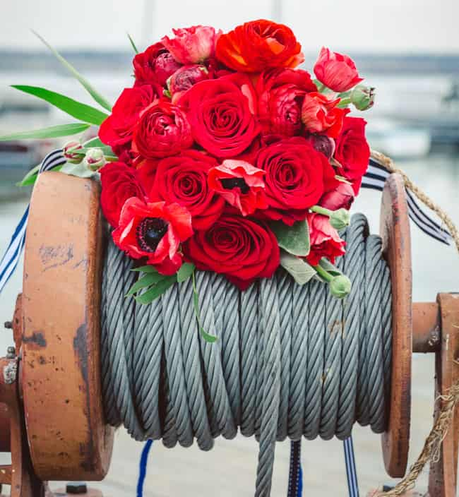 a nautical wedding bouquet of red roses and ranunculus, some greenery and striped ribbons is chic