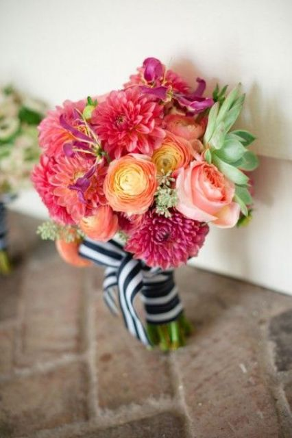 a colorful nautical wedding bouquet of pink, red, orange blooms, a succulent and a striped bouquet wrap is amazing