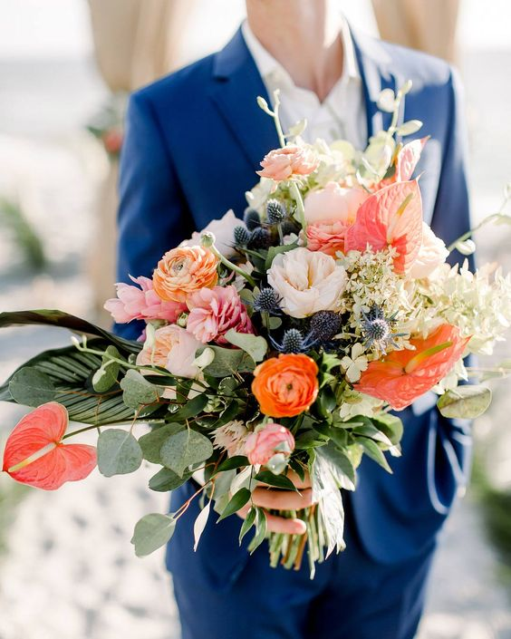 a colorful nautical wedding bouquet of orange and pink ranunculus and peonies, thistles, lots of leaves and greenery is wow