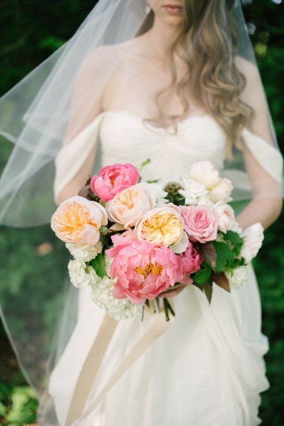 a bright wedding bouquet of peachy, pink and white peonies and peony roses plus greenery for a bold nautical wedding