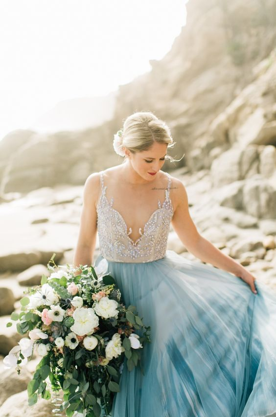 a gorgeous wedding dress with a neutral embellished bodice and a blue tie-dye skirt plus a covered neckline is wow