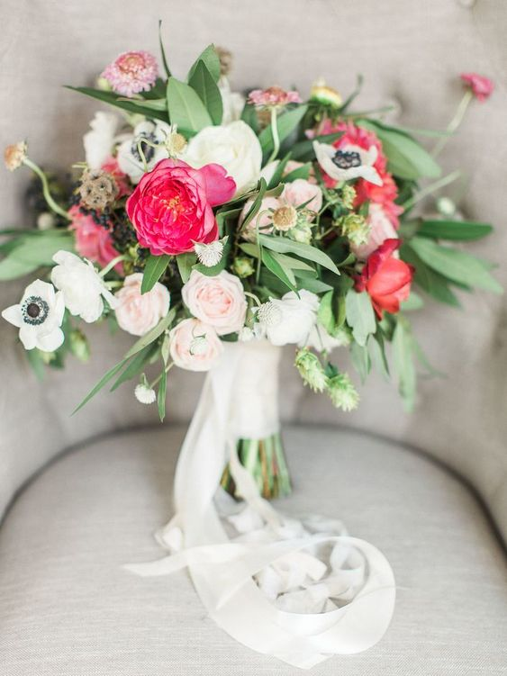 a modern nautical wedding bouquet of white anemones, blush and hot pink roses, thistles and greenery and white ribbons
