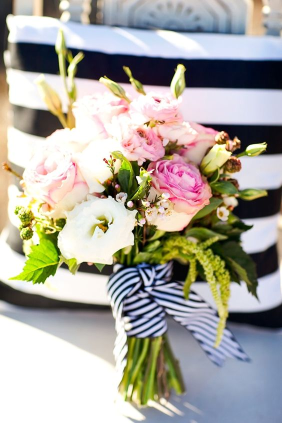a bright nautical wedding bouquet of pink and white roses, greenery, waxflower and a striped ribbon is amazing