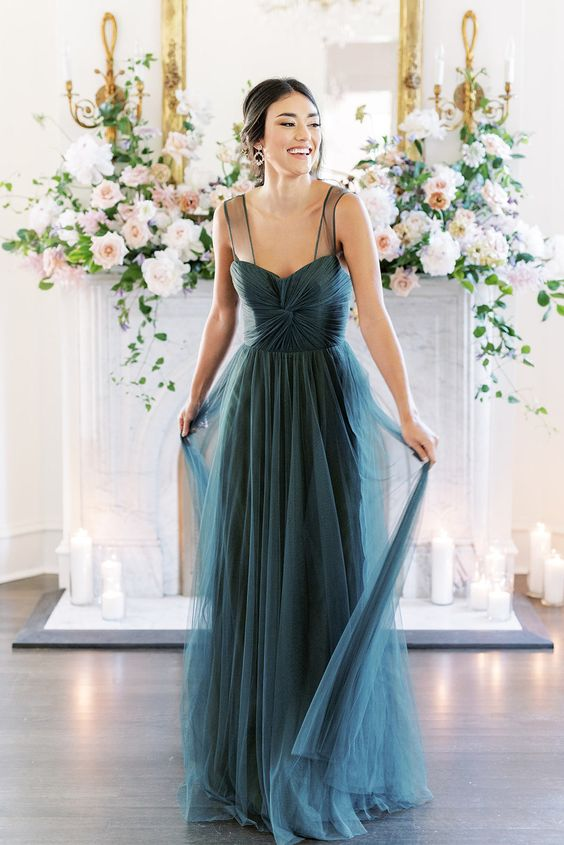 a grey blue wedding dress with a fitting wrap bodice and an A-line skirt, sheer thick straps and pleating is refined