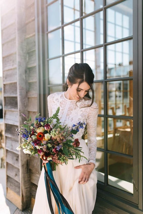 a colorful nautical wedding bouquet of purple, burgundy, blush roses, greenery, astilbe and grasses with teal ribbons