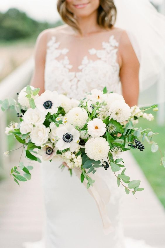 a beautiful modern nautical wedding bouquet of white anemones, dahlias, greenery, privet berries and some blooming branches
