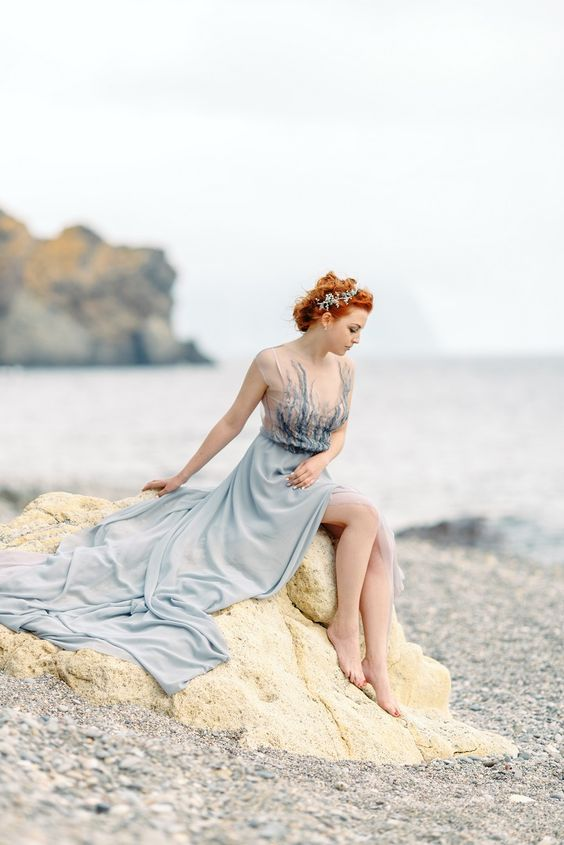 a light blue A-line wedding dress with lace embellished bodice and cap sleeves plus a train for a sea nymph look