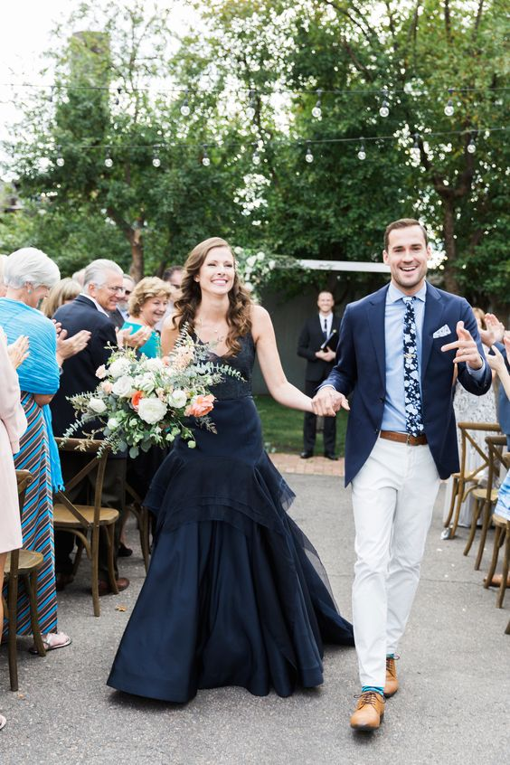 a midnight blue wedding dress with a fitting bodice and an A-line skirt with tiers, a deep neckline and no sleeves