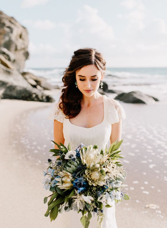 a chic modern nautical wedding bouquet with king proteas, white anemons, blue blooms and thistles, greenery is a beautiful idea for a seaside wedding