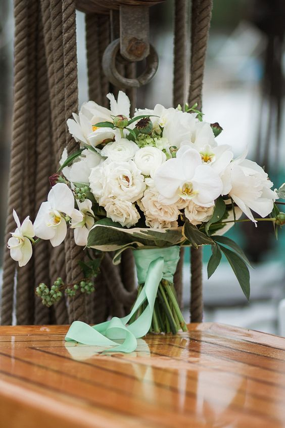 a gorgeous nautical wedding bouquet of white ranunculus and orchids, berries and greenery plus bright green ribbons