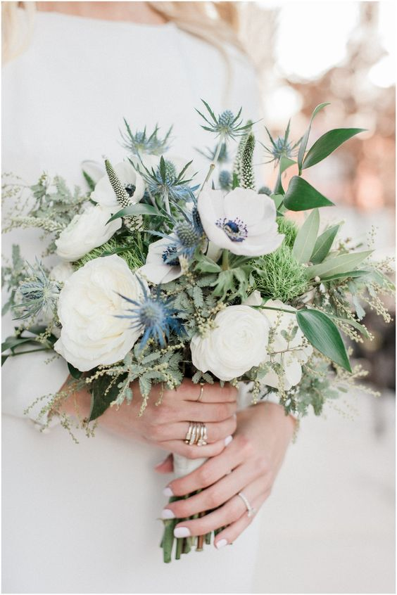 a heavenly beautiful nautical wedding bouquet of white roses and ranunculus, thistles, astilbe, greenery of various kinds