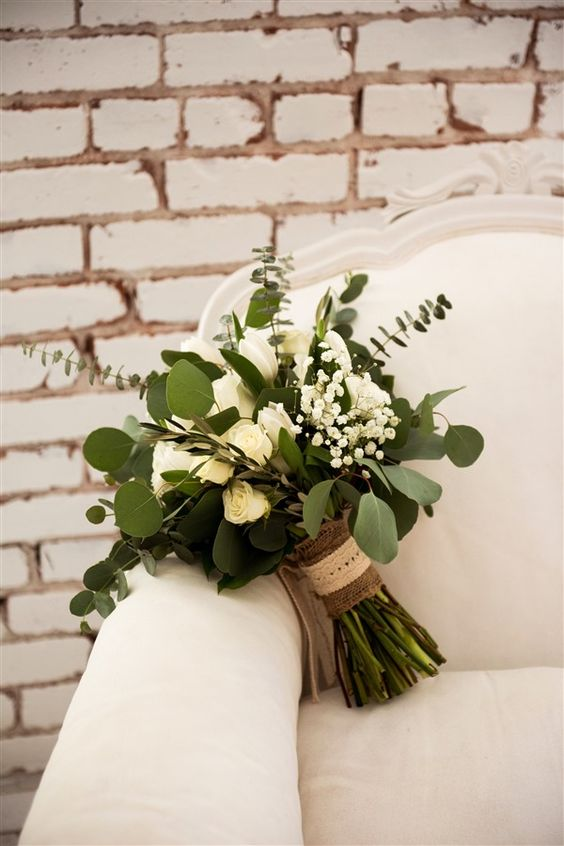 a lovely wedding bouquet of white roses, baby's breath, eucalyptus and with a burlap wrap is great for a nautical wedding