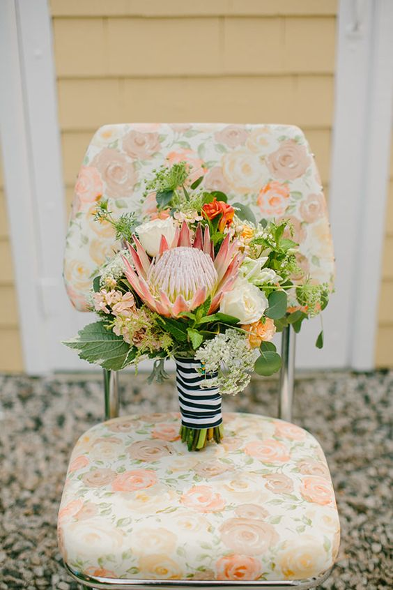 a nautical wedding bouquet of white and orange roses, a king protea, greenery and a striped ribbon for a bouquet wrap