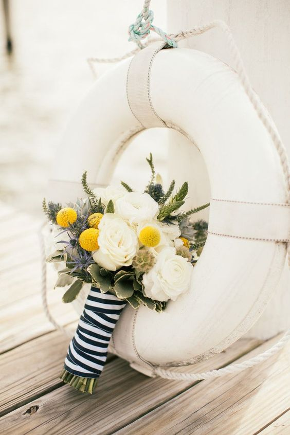 a nautical wedding bouquet of white roses, astilbe, billy balls, thistles and leaves plus seed pods and a striped ribbon for a wrap