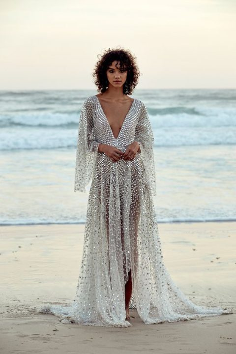 a sparkling silver A-line dress with a plunging neckline and bell sleeves that is inspired by fish scales
